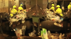 Excellent shot of workers in a recycling center sorting trash on conveyor belts. - stock footage