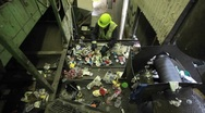 Stock Video Footage of High angle view of workers sorting trash at a recycling center.