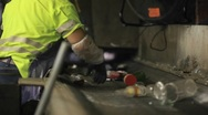 Stock Video Footage of Workers sort trash on a conveyor belt at a recycling center.