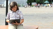 Young happy teenager with tablet computer sitting in the city HD Stock Footage