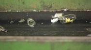 Stock Video Footage of Bottles and cans move along a conveyor belt at a recycling center.