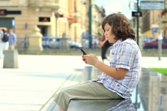 Happy young boy sending sms, texting in the city NTSC - stock footage