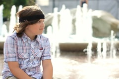 Happy young boy sitting by the fountain, slow motion NTSC Stock Footage