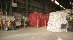 Step motion of a skip loader moves aluminum cans at a recycling center. - stock footage