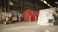 Stock Video Footage of Step motion of a skip loader moves aluminum cans at a recycling center.