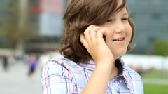 Young boy talking on mobile phone in the city HD Stock Footage