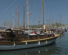 Pan from gulets in harbour to moving gulet Stock Footage