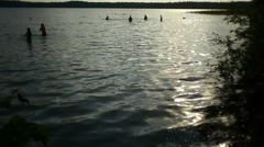 People playing in the water, people passing along the shore Stock Footage
