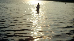 Girl walking in from the sea at sunset Stock Footage