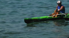 A man rows a kayak fast across the water. Stock Footage