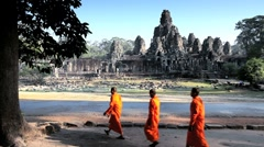 Three Monks walking outside the Bayon temple, Angkor, Siem Reap, Cambodia Stock Footage