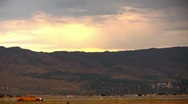 Bright Yellow Truck Trives Across Mountain Skyline Sunset Stock Footage