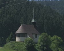 Zoom out from chapel at edge of forest Stock Footage