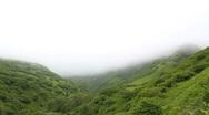 Fog Rolls Over Green Hills Stock Footage