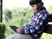 Young happy teenager with tablet computer in the park, dolly shot NTSC Stock Footage