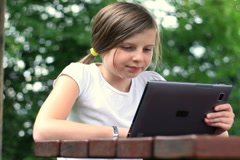 Young teenage girl with tablet computer outdoors, dolly shot NTSC - stock footage