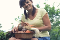 Young happy woman holding basket full of fresh vegetables in the garden Stock Footage