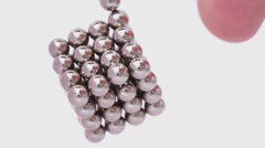 Magnet balls in cubic structure hangs, finger push it and cube begin to rotate Stock Footage