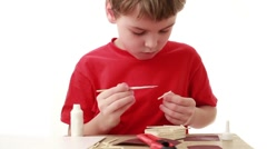 Boy put adhesive to match, in front of him on table unfinished house from Stock Footage