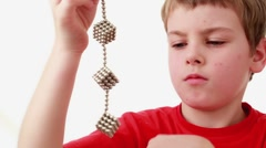 Boy hold chain compound of magnet spheres cubic structures - stock footage