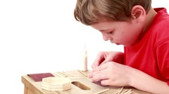 Boy whet match using sandpaper which lies on table for this Stock Footage