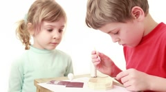 Girl watch on how boy apply glue on stick and attach to wall of match house Stock Footage