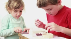 Two kids building match house Stock Footage