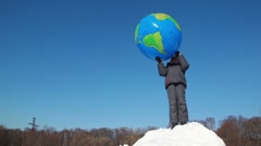 Boy stand on snow pile and hold inflated ball over head Stock Footage