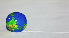Inflated ball with earth texture roll by snow Stock Footage
