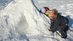 Two kids boy and girl play on snow pile at winter day Stock Footage