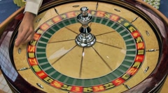 Dealer throwing ball to roulette game - stock footage