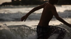 Stock footage two boys playing in the waves of the sea at sunset Stock Footage