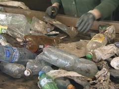 Recycling. PET bottles ride escalator and man hands sorts them. Stock Footage