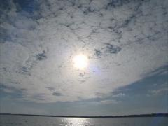 Sun shining through clouds creating ripple glare on the water. Stock Footage