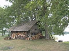 Old wooden woodshed made of logs with slate roof at lake shore. Stock Footage