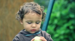 Young baby boy eating fresh green apple, outdoors Stock Footage