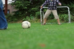 Father and son playing soccer in the garden, slow motion Stock Footage