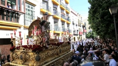 Costaleros bearing a Trono a religious float, through the streets of Malaga - stock footage