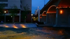 Worlds fair park conference center area seen across waterfall at dusk Stock Footage