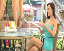 Young woman in a cocktail dress looking menu Stock Footage