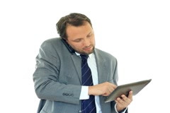 Businessman with tablet computer and cell phone, isolated on white NTSC Stock Footage