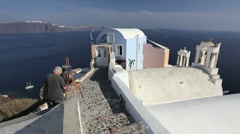 Artist painting in the town of Oia, Island of Santorini, Greece, Europe Stock Footage