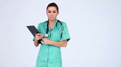 Young beautiful female doctor on white background Stock Footage
