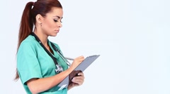 Cute young female doctor on white background making notes Stock Footage