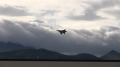 Air Force jet soaring past mountains up into cloud filled skies (HD) c Stock Footage