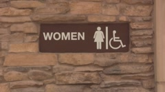 Womens bathroom sign at the park brick wall Stock Footage