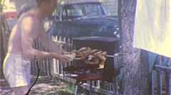 Man BBQs Chicken Barbecue GRILLED Summertime 1960s Vintage Film Home Movie 306 Stock Footage