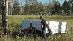 Men setting up camp trailer mountain meadow P HD 9526 Stock Footage
