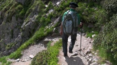 A man hikes down a mountain with a backpack. Stock Footage