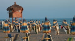 Closed umbrellas and chairs on the beach at sunset Stock Footage